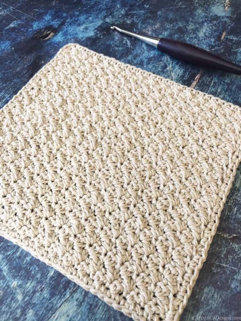 Crochet washcloth with texture in beige cotton yarn on blue background.