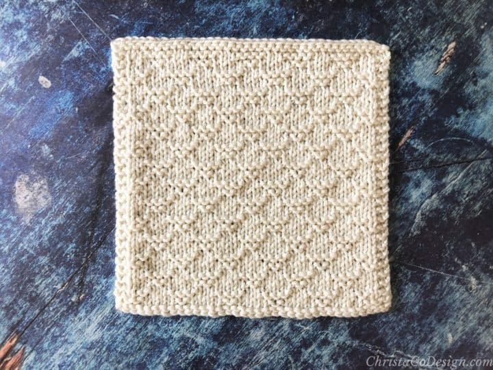 Cream colored knit blanket square with easy texture on blue background.