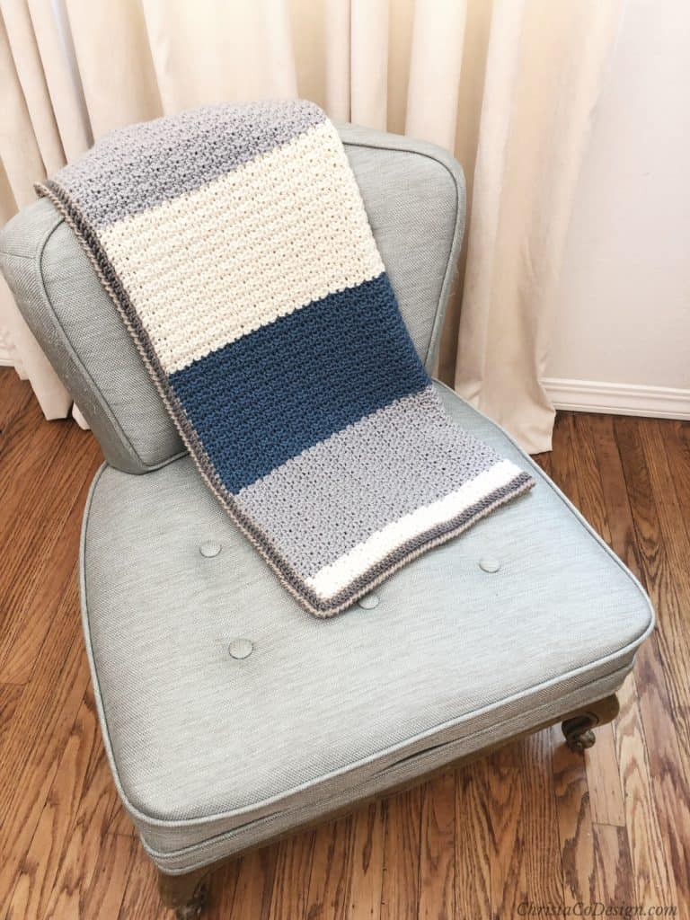 Striped grey, blue and cream crochet baby blanket on blue vintage chair.