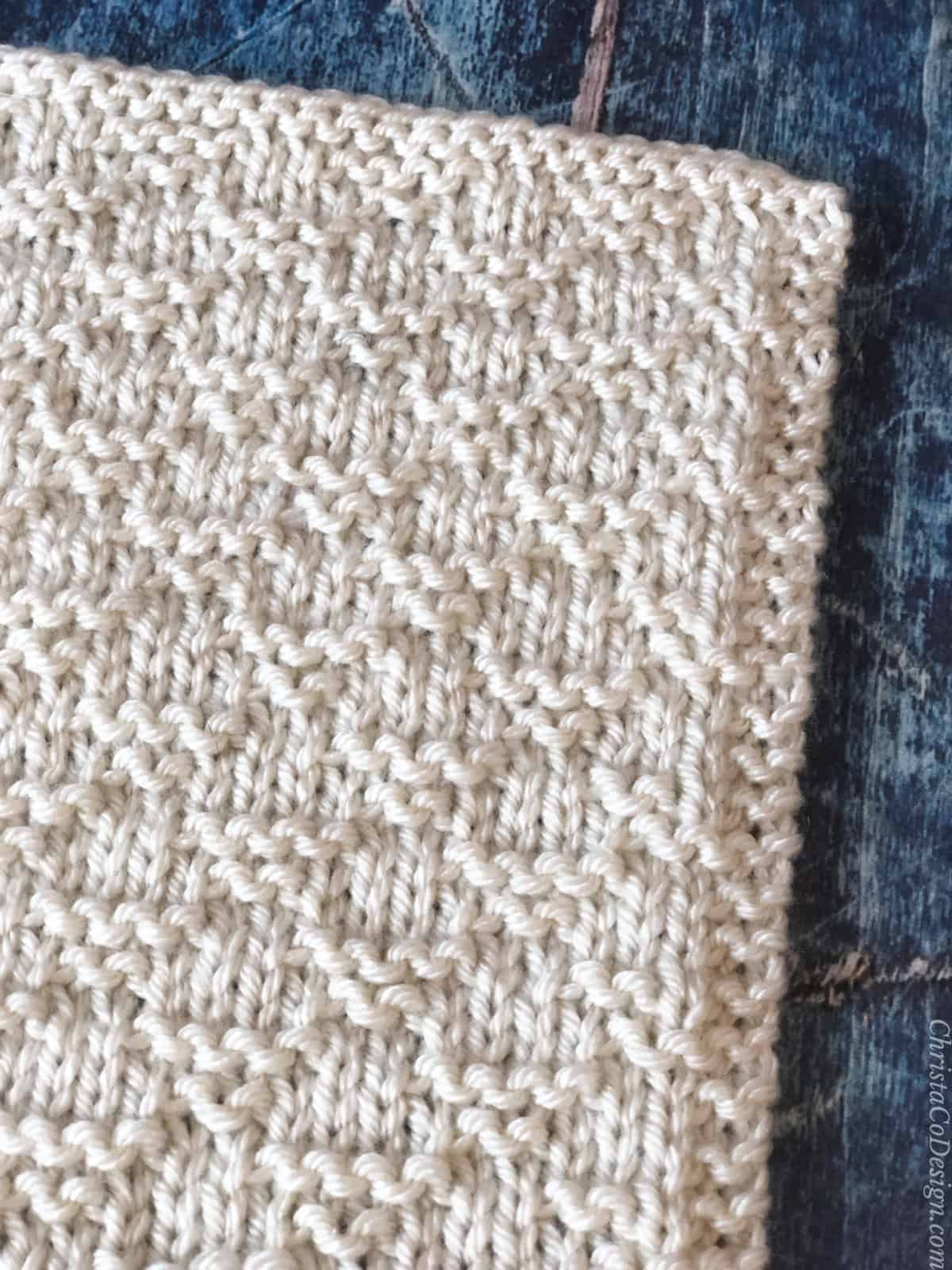 Close up of stitches creating triangle pattern in knit blanket square free pattern.