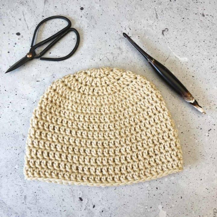 Double crochet beanie in beige yarn, scissors, crochet hook on grey speckled background.