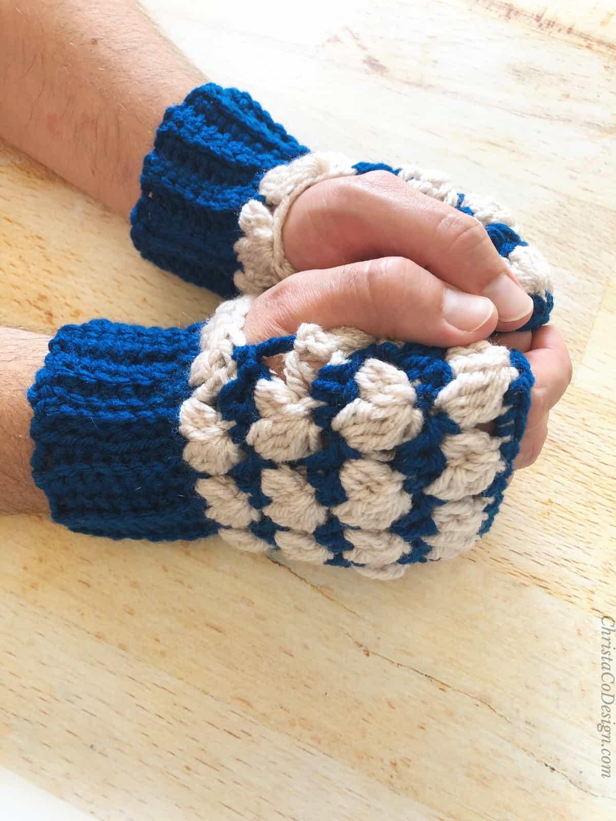 Man's hands in blue and cream crochet fingerless gloves.