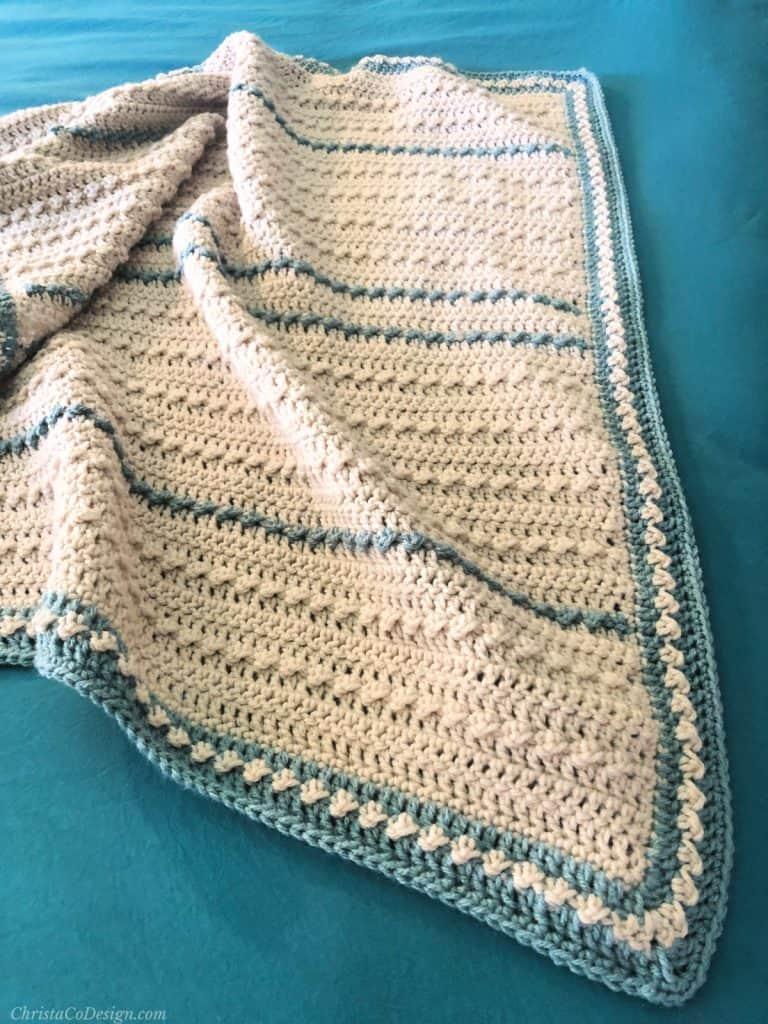 Corner of baby blanket crochet pattern on blue bed.