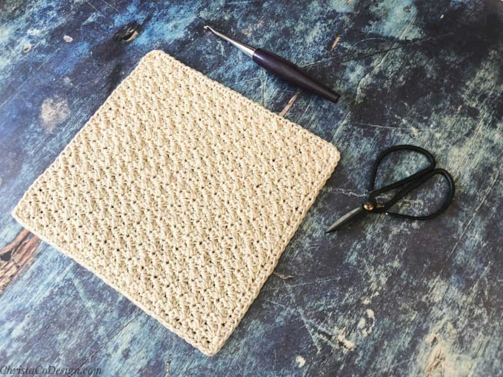 Square crochet washcloth in beige on blue back ground.