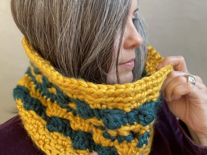 Woman in gold cowl crochet free pattern and teal stripes.