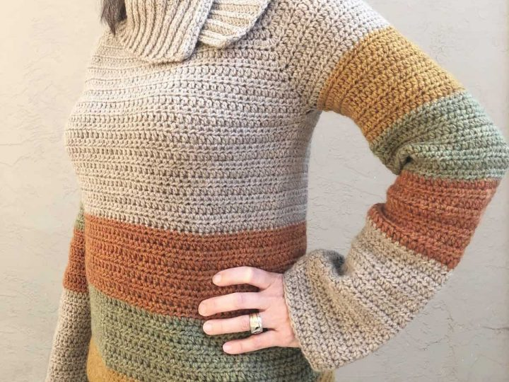 Woman in crochet sweater with bronze, green and gold stripes.