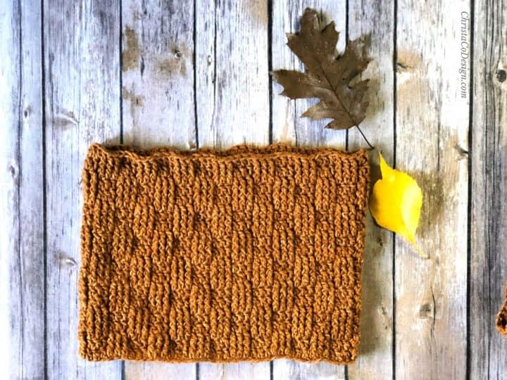 Basketweave cowl crochet pattern in rust yarn on wood.