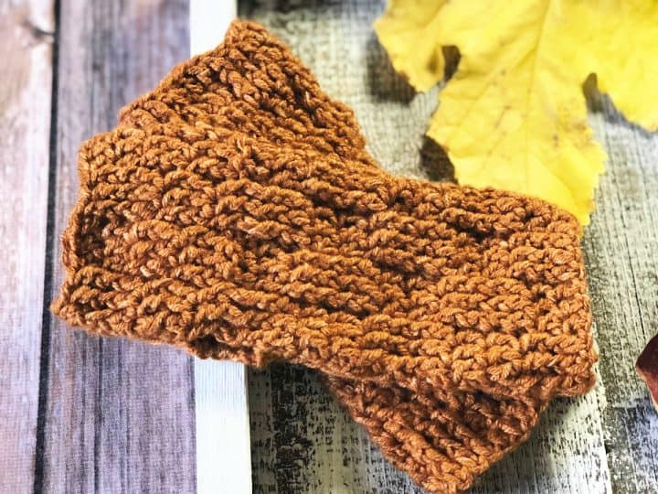 Women's crochet fingerless gloves crossed on wood square with leaves.