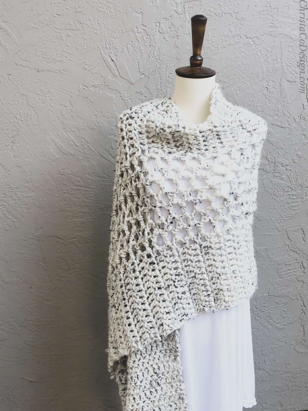 Rectangle crochet shawl wrapped on mannequin in white.