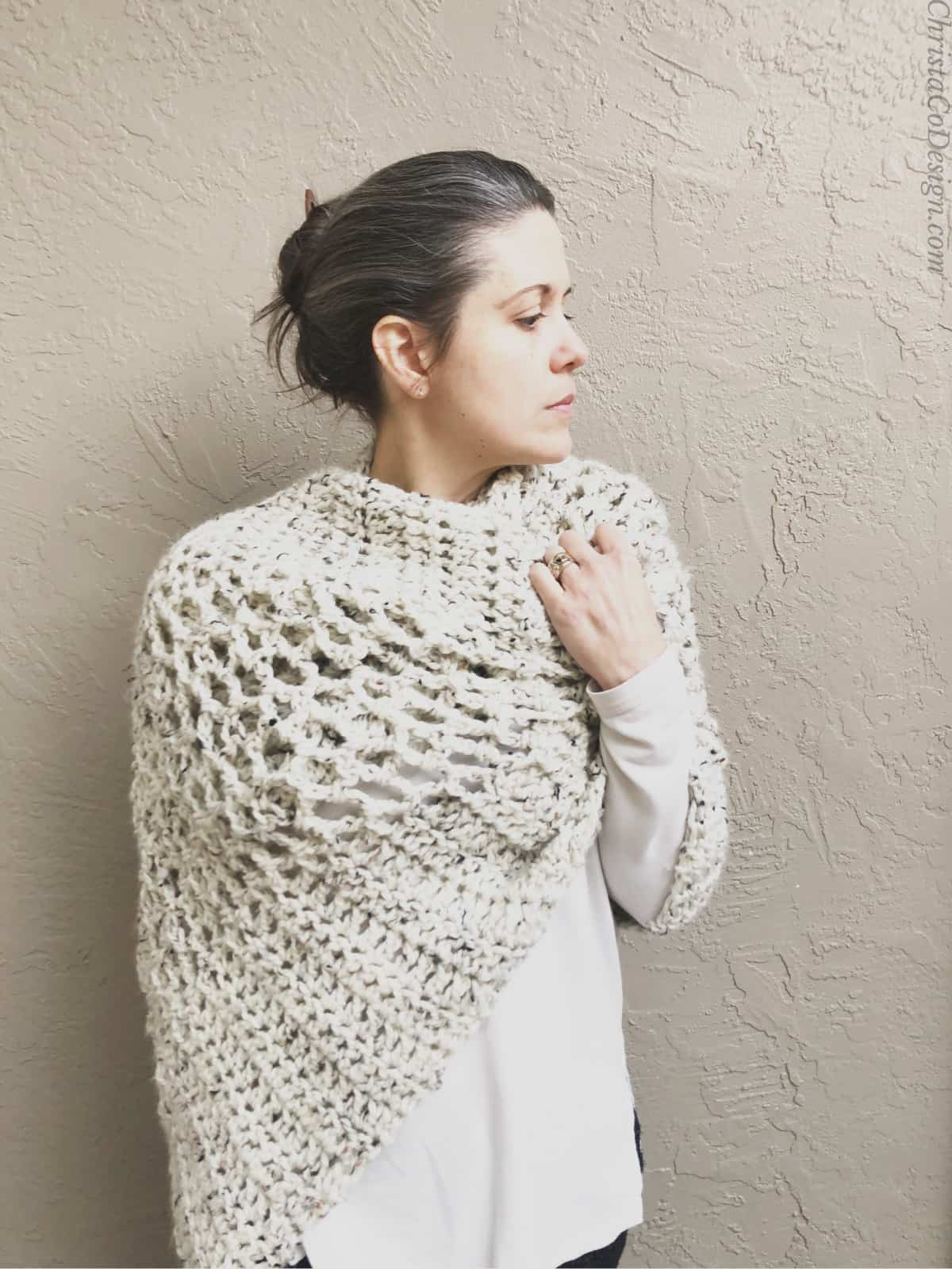 Front view of woman in cream colored easy rectangular crochet shawl pattern looking to the side.